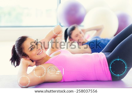 Two fit young women doing pilate exercises against fitness interface - stock photo