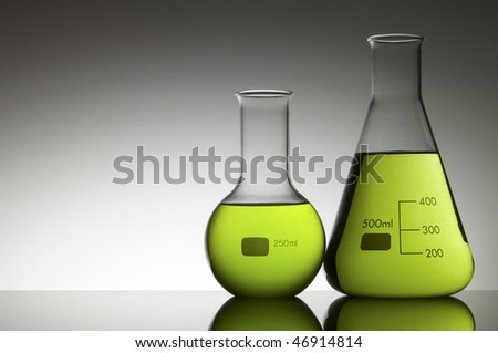 two flasks with liquid bright green and white background