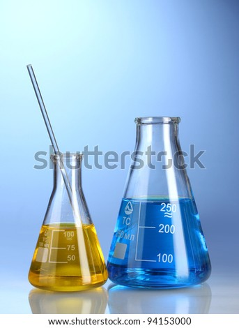 Two flasks with yellow and blue liquid with reflection on blue background