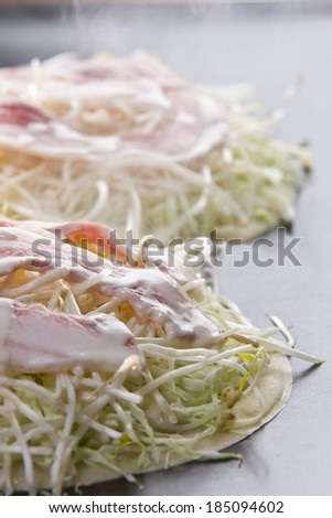 Two flat breads stacked with beansprouts, lettuce, and bacon on a grill. - stock photo