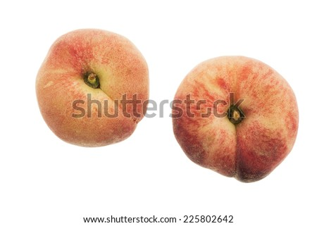 Two flat peaches isolated on white - stock photo
