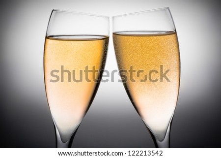 two flutes of champagne with gold bubbles on a grey background