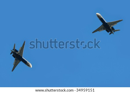 two flying planes isolated over blue sky - stock photo