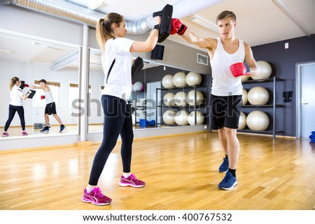 Two focused people training boxing at the fitness gym - stock photo