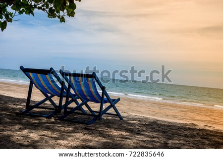Two folding chair with blue color on the beach in sunlight with sea view/Nature and a holidays