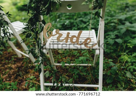 Two Folding Chairs In Heavy Foliage With Decorative Signs