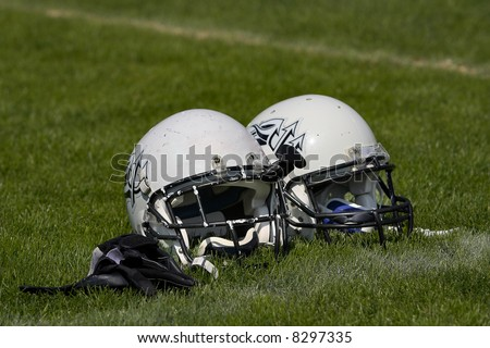 Two football helmets placed side by side on the playing field. - stock photo