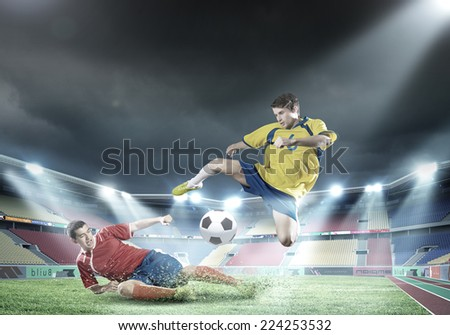 Two football player fighting for ball at stadium