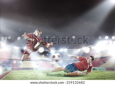 Two football player fighting for ball at stadium - stock photo