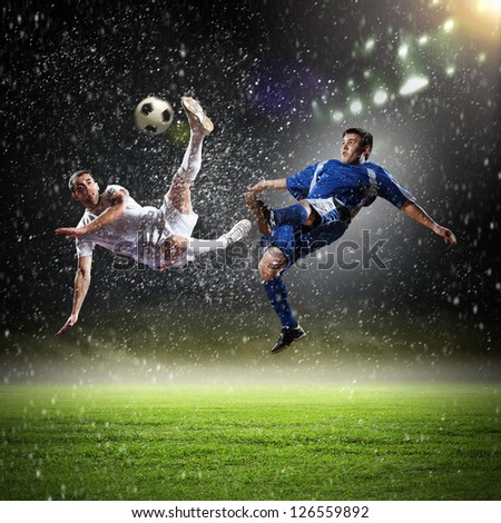 two football players in jump to strike the ball at the stadium under rain - stock photo