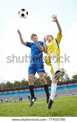Two footballers jumping and looking at ball on grass-field during game - stock photo