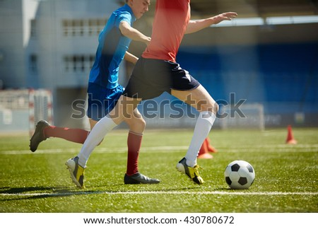Two footballers running down field after ball - stock photo