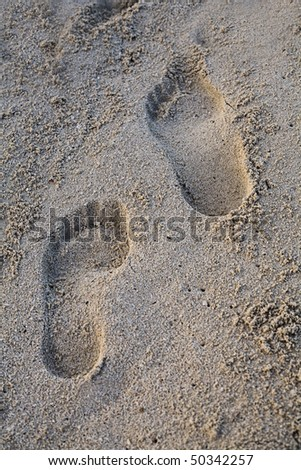 Two footprints in fine white caribbean sand with morning sun - stock photo