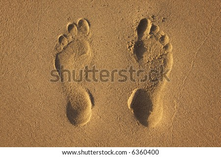 Two footprints in the sand on the beach. - stock photo