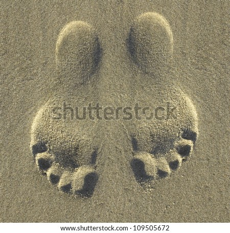 two footprints on a beach - stock photo