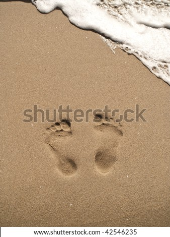 two footprints on sand with white water wave. - stock photo