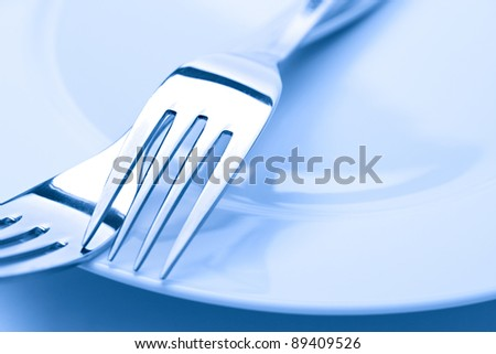 Two forks on a plate in blue light
