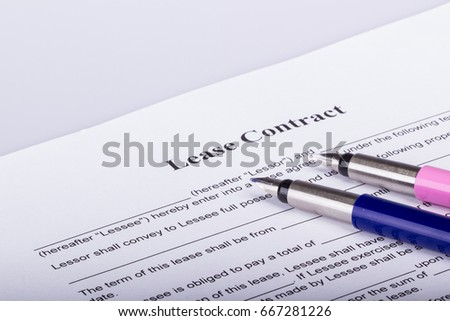 Two fountain pens on the first page of a lease contract, waiting for both parties to sign