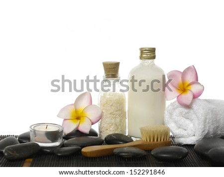 Two frangipani, brush, towel, salt,oil in glass, pebbles on mat