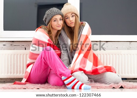 Two freezing girls near the heater - stock photo