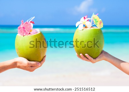 Two fresh coconut cocktails with umbrellas in hands - stock photo
