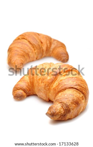 Two fresh croissant isolated over white background - focus on close one