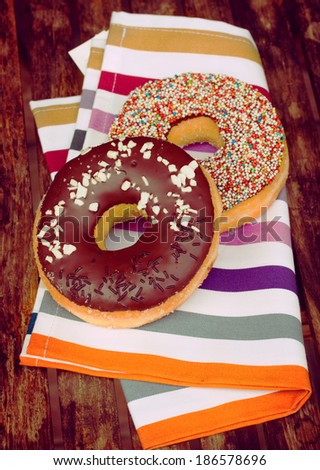 two fresh donuts laying on wooden  table
