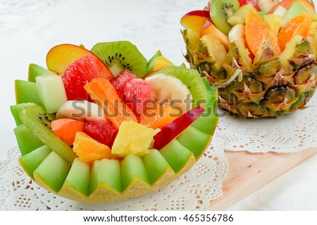 Two fresh fruit salad with kiwi, banana, peach, orange, red orange, apricot and melon in handmade melon and pineapple bowl.
