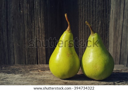 Two fresh green pears against an old textural wooden surface. - stock photo