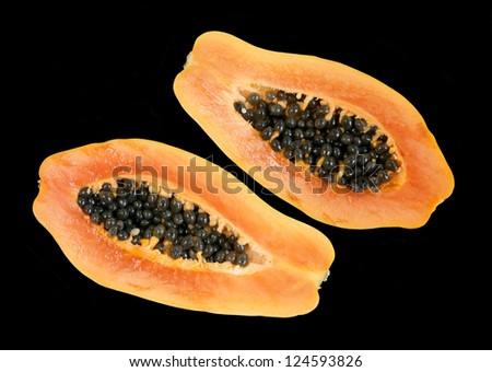 Two fresh  half papaya isolated on black background - stock photo