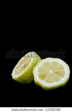 Two fresh lemon fruit halfs isolated on black background