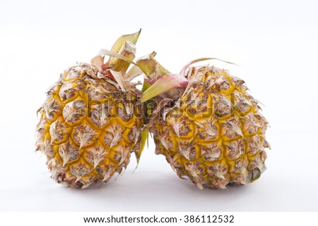 two fresh mini pineapple fruits on a white background
