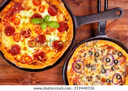 Two fresh pan pizzas on iron skillets , wooden background , top view - stock photo