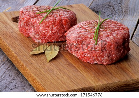 Two Fresh Raw Beef Burgers with Chives and Bay Leaf on Wooden Cutting Board closeup on Rustic Wood background - stock photo