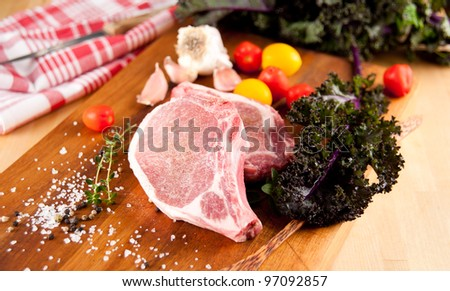 Two Fresh Raw Pork Chops Ready to be Grilled and Served with Red Kale - stock photo