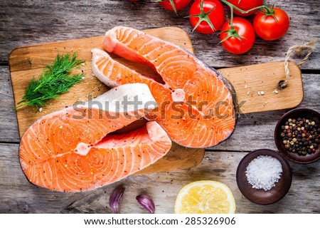 Two fresh raw salmon steaks with salt, peppers, lemon, tomatoes and dill on the rustic table - stock photo
