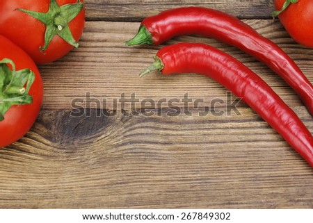 Two Fresh Red Hot Chili Peppers And Three Tomatoes On The Rustic Wood Kitchen Table. Background With Copy Space. Ingredients for Soup, Salad, Paste - stock photo