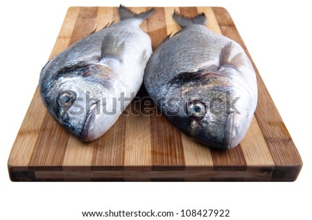 two fresh sea bream on a cutting board on the isolation of a white background