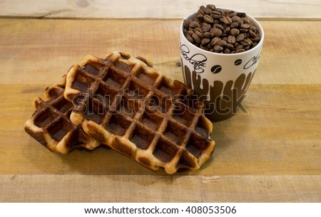Two fresh waffles with cup full of coffee beans. Good morning - stock photo