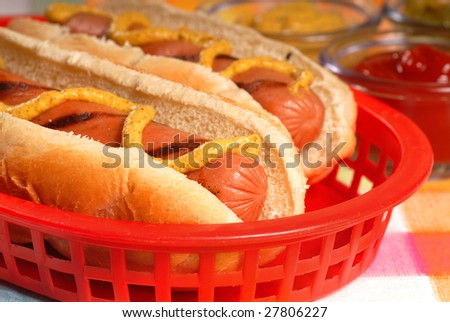 Two freshly grilled hot dogs in a basket with condiments - stock photo