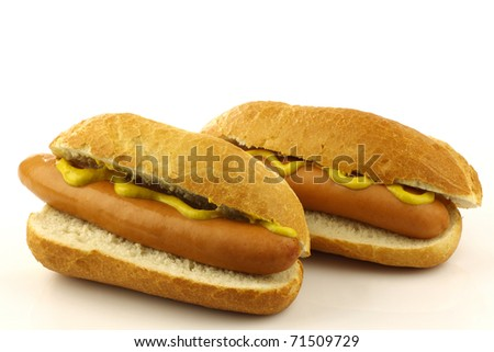 two freshly homemade hot dogs with mustard on a white background - stock photo