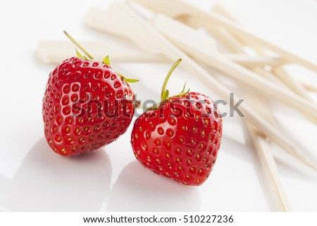 Two freshly picked strawberries on white plate with wooden fondue sticks.