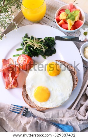Two fried eggs and bacon served with orange juice and fruit salad.