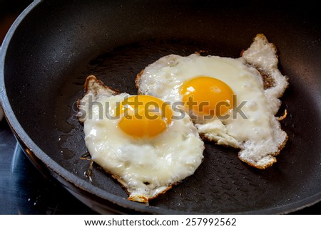 two fried eggs in a black pan, breakfast preparation - stock photo