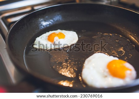 Two fried eggs with bacon and onion, tomato and bread on the side