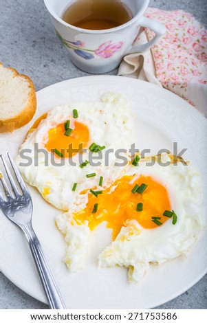 Two fried eggs with chives on white plate. studio shot - stock photo