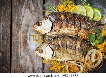 two fried fish with fresh herbs and lemon on wooden table - stock photo