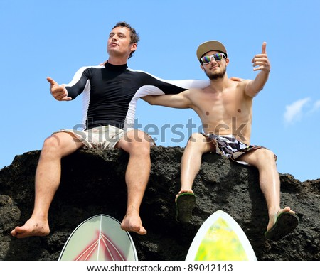 Two friend surfer sitting on a rock showing sign OK - stock photo