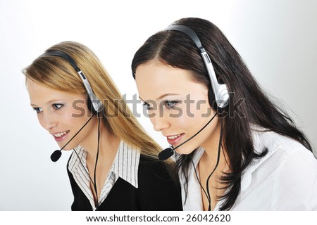 Two Friendly Customer Representative with headset smiling during a telephone conversation