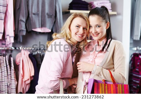 Two friendly females in smart casual looking at camera in department store - stock photo